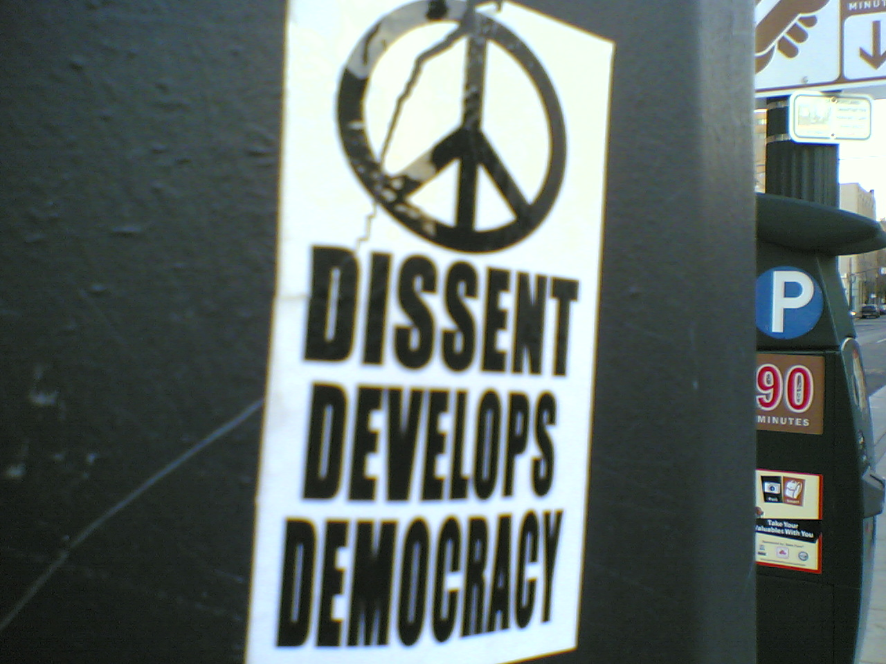 "Sticker advocating dissent: ""dissent develops democracy"", accompanied by a peace symbol. Photo taken in Portland, Oregon. Photographer is Jason Wilson"